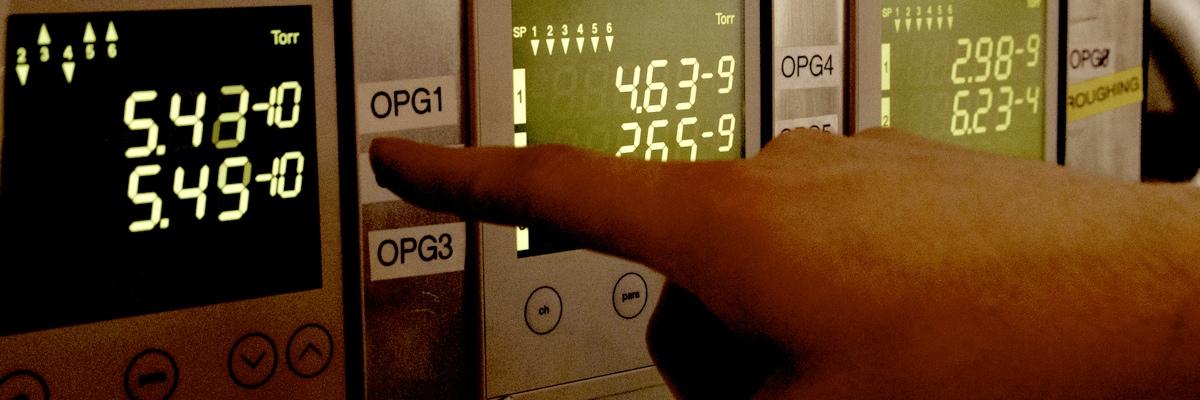 Finger zeigt auf Messgerät mit Druckanzeigen um 10 hoch minus 9 Torr