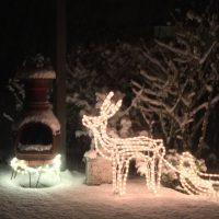 Beleuchteter Weihnachtsschmuck in Schneelandschaft