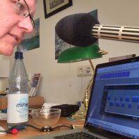Mann spricht in ein Mikrofon, im Hintergrund Audioschnittsoftware auf einem Notebook
