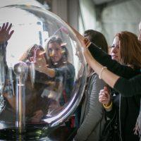 Jugendliche experimentieren mit einer Plasmakugel