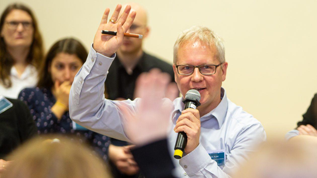 Ein freundlich schauender Mann mit Mikrofon sitzt in einer Gruppe Menschen und meldet sich mit einer Hand.