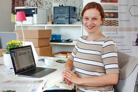 Freundlich lächelnde junge Frau sitzt an einem Schreibtisch. Auf dem Tisch befinden sich ein aufgeklapptes Notebook, eine Kaffeetasse, ein Zeitschrift und eine Topfblume.