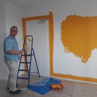 Ein Mann steht neben einer Stehleiter und lächelt. Er hält eine Farbrolle in der Hand, ein Farbeimer steht auf dem Boden. Die Wand ist halb mit der Farbe gestrichen.